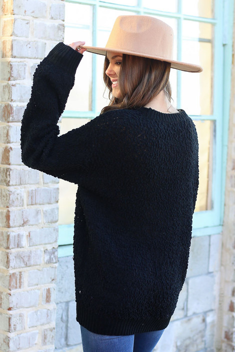 Model wearing the Popcorn Knit Oversized Top in Black with high rise skinny jeans and wide brim fedora from Dress Up Boutique Back View