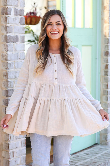 Model wearing the Ivory Tiered Babydoll Tunic with high rise jeans from Dress Up Boutique front view
