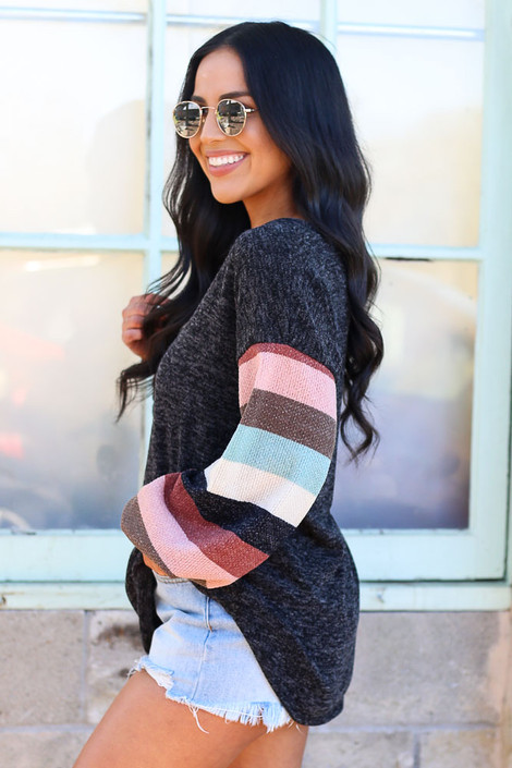 Model wearing the Black Statement Sleeve Brushed Knit Top with denim shorts and sunglasses Side View