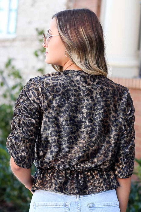 Model wearing the Draped Sleeve Leopard Blouse with high rise jeans and sunglasses from Dress Up Back View