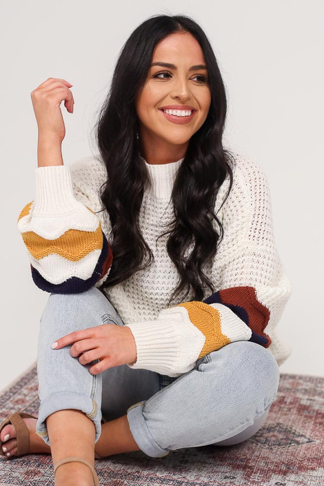 Model wearing the Statement Sleeve Oversized Knit Top with light wash jeans