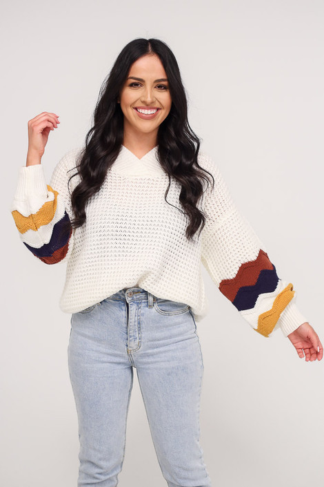 Dress Up model wearing the Statement Sleeve Oversized Knit Top with light wash jeans