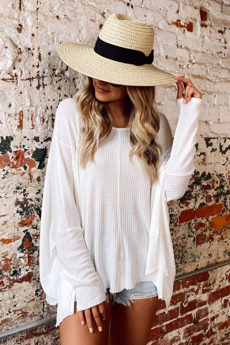 Model wearing the Blake Oversized Top in Ivory with a wide brim hat