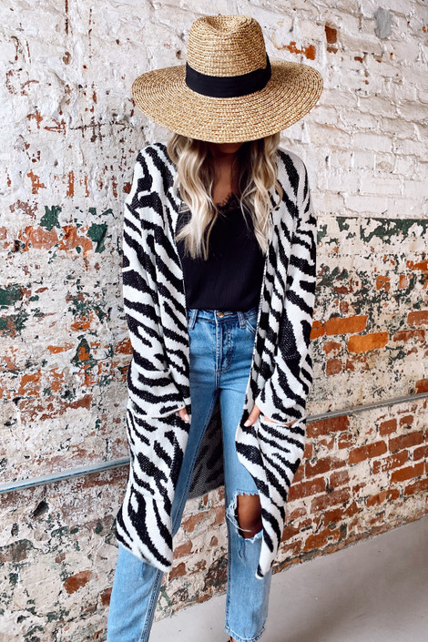 Black - Model wearing the Zebra Longline Luxe Knit Cardigan with a wide brim hat