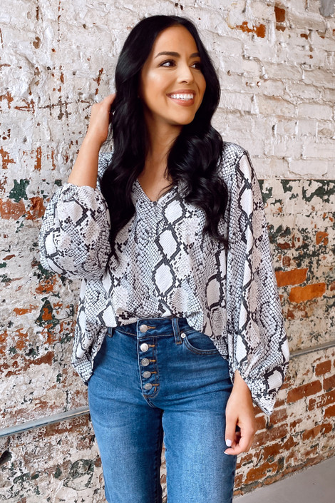 Model wearing the Snakeskin Balloon Sleeve Blouse with high rise jeans from Dress Up