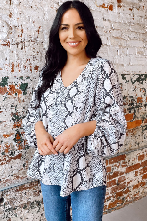 Model wearing the Snakeskin Balloon Sleeve Blouse front tucked into jeans from online dress boutique
