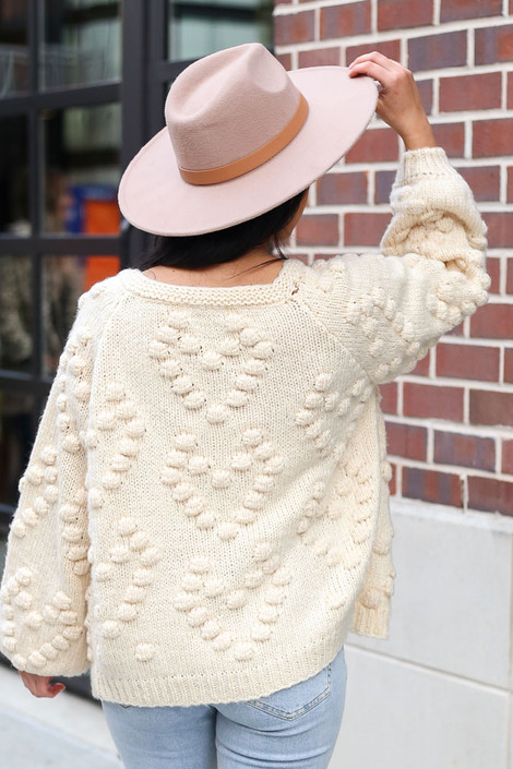 Dress Up model wearing the Pom Pom Heart Knit Cardigan in Ivory with a wide brim hat