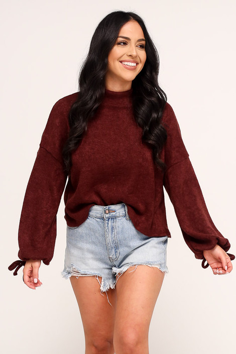 Model wearing the Balloon Sleeve Knit Top in Burgundy with high rise denim shorts from Dress Up