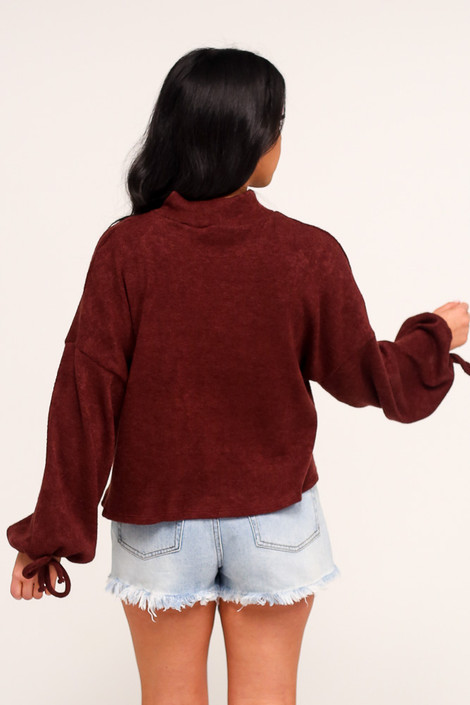 Model wearing the Balloon Sleeve Knit Top in Burgundy with high rise denim shorts from Dress Up Back view
