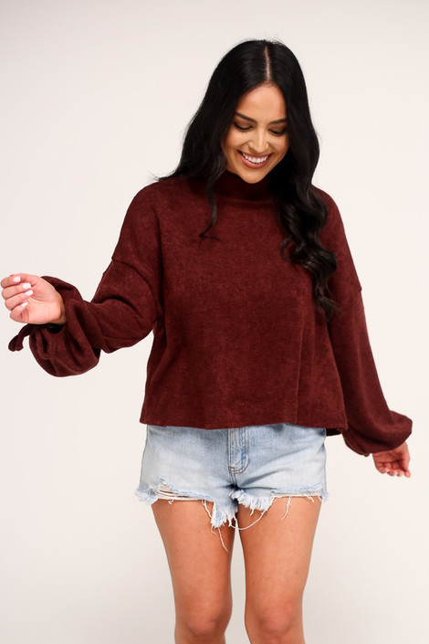 Model wearing the Balloon Sleeve Knit Top in Burgundy with high rise denim shorts from Dress Up Front View