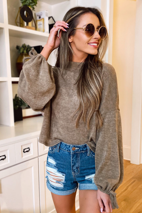 Model wearing the Balloon Sleeve Knit Top in Taupe with high rise jean shorts from Dress Up Boutique Front View