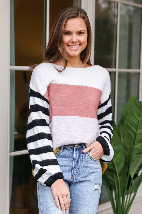 Blush - Model wearing the Oversized Color Block Knit Top tucked into light wash jeans from Dress Up