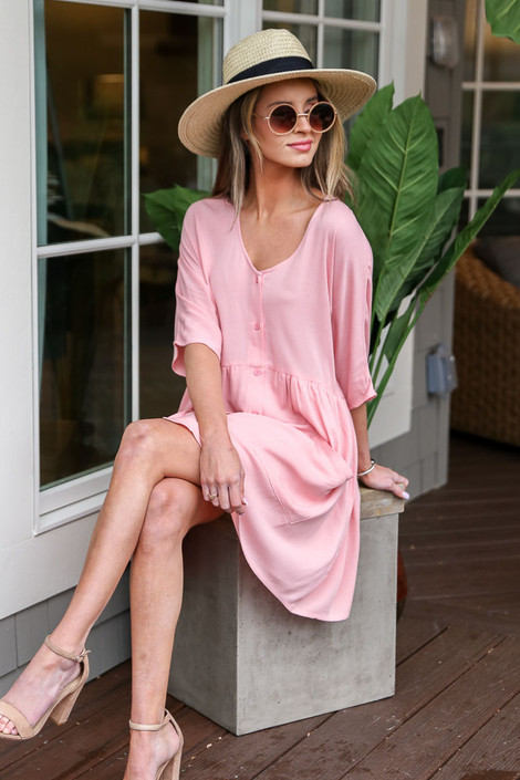 Model wearing the Blush Button Front Babydoll Dress with wide brim fedora and sunglasses from Dress Up Boutique Sitting View