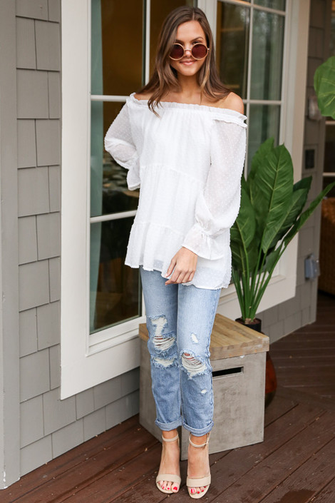 Dress Up model wearing the Swiss Dot Tiered Babydoll Tunic off the shoulder with light wash distressed denim jeans and nude heels