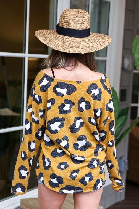 Model wearing the Mustard Leopard Lightweight Knit Top with light wash jeans from Dress Up Boutique Back View