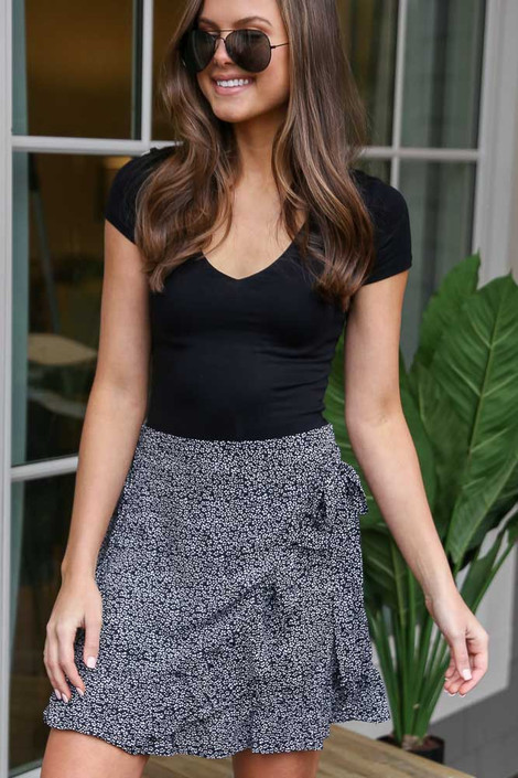 Model wearing the Floral Wrap Skirt in Black with Black bodysuit and sunglasses from Dress Up Front View