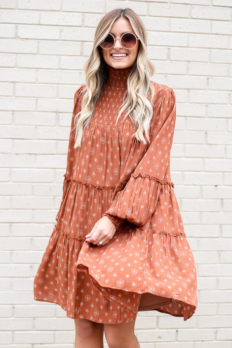 Model wearing the Smocked Mock Neck Tiered Dress in Rust
