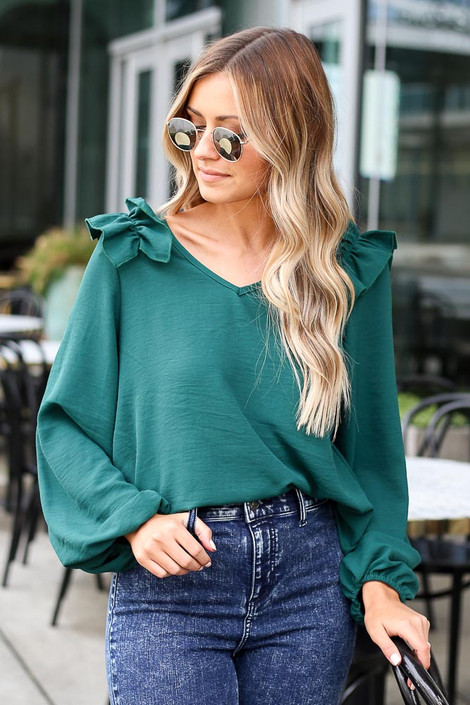 Model wearing the Ruffle Shoulder Blouse with dark wash jeans