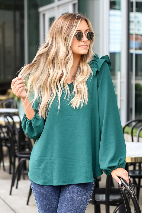 Model wearing the Ruffle Shoulder Blouse in Green from Dress Up
