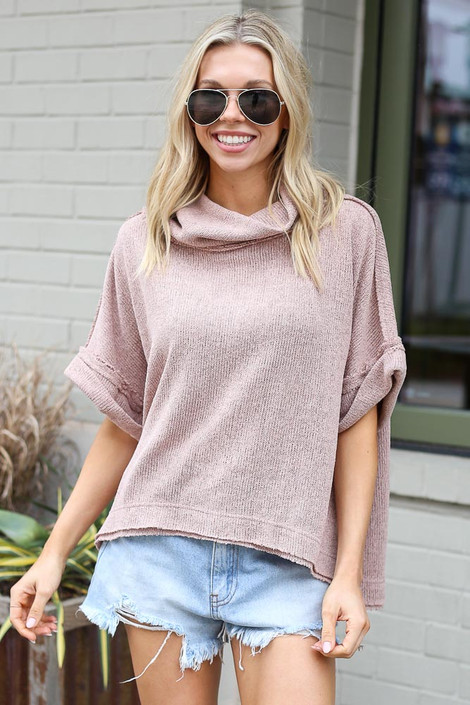 Model wearing the Cowl Neck Oversized Knit Top in Taupe with denim shorts