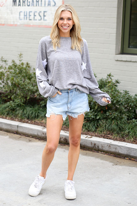 Model wearing the Star Sleeve Oversized Pullover in Heather Grey with denim shorts and white sneakers