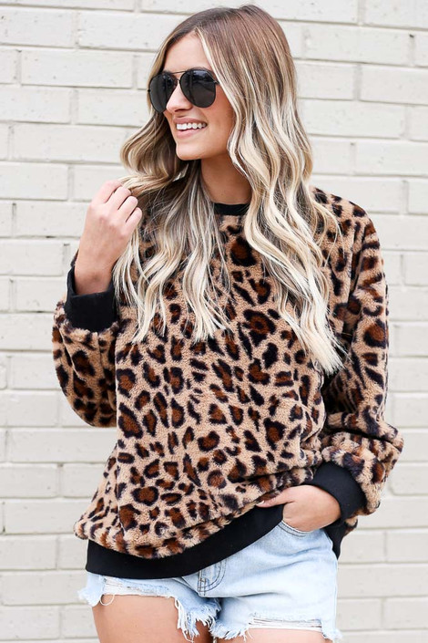 Model wearing the Leopard Faux Fur Pullover with high rise shorts and aviator sunglasses