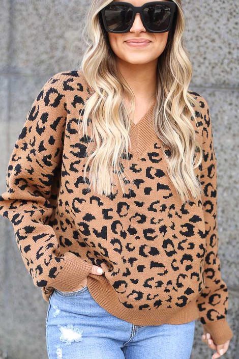Model wearing the Camel V Neck Leopard Luxe Knit Top with distressed jeans and block heel booties Close Up