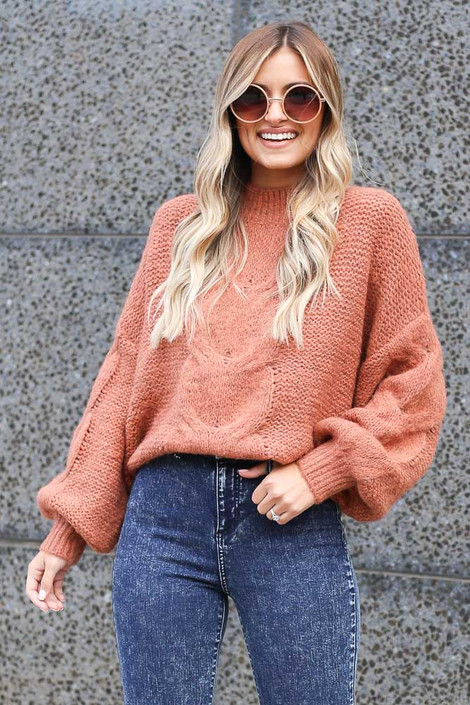 Model wearing the Mock Neck Cable Knit Top in Rust Front View