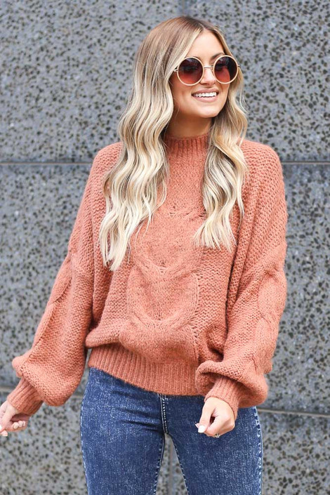 Model wearing the Mock Neck Cable Knit Top in Rust with high rise jeans and sunglasses from online dress boutique