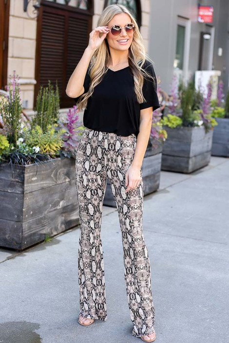 Model wearing the Snakeskin Stretch Knit Flare Pants with a black tee