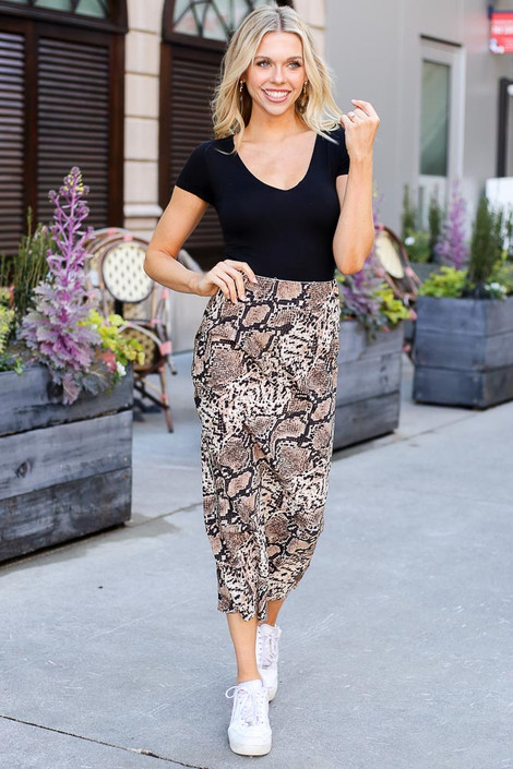 Model wearing the Snakeskin Midi Skirt with a black bodysuit and white sneakers