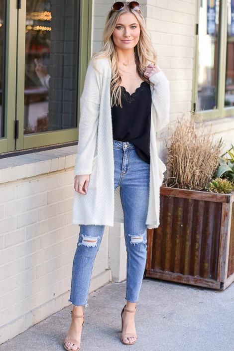 Model wearing the Ivory Fuzzy Knit Cardigan with black tank top and high rise distressed jeans