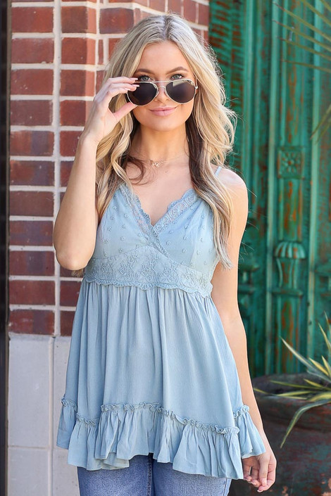 Model wearing the Lace Tie-Back Tank in Sage with high rise denim shorts and polarized aviator sunglasses Front View