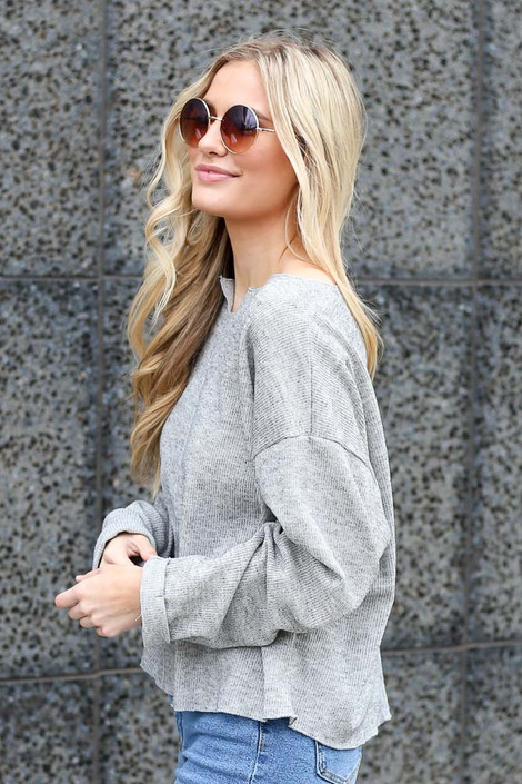 Model wearing the Ribbed Knit Oversized Top in Grey with high rise jeans Side View