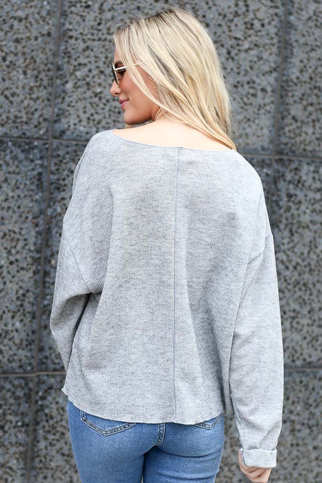 Model wearing the Ribbed Knit Oversized Top in Grey with high rise jeans Back View