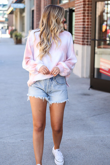 Model wearing the Brushed Knit Oversized Tie-Dye Pullover with denim shorts and white sneakers
