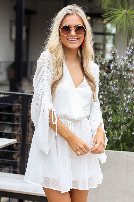Model wearing the Gathered Sleeve Swiss Dot Romper with cute sunglasses