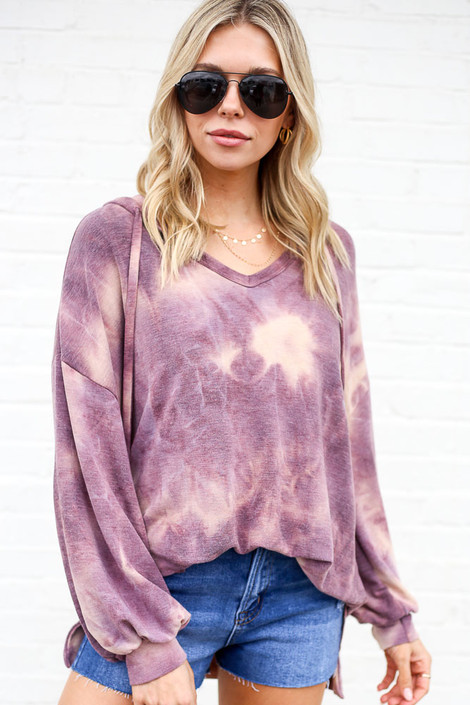 Model wearing the Tie-Dye Oversized Pullover Hoodie with distressed jean shorts