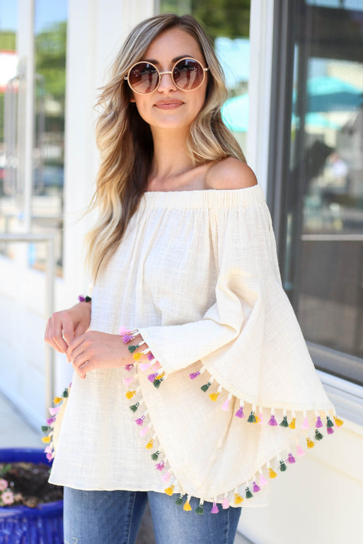 Model wearing Ivory Off the Shoulder Bell Sleeve Tassel Top Front View