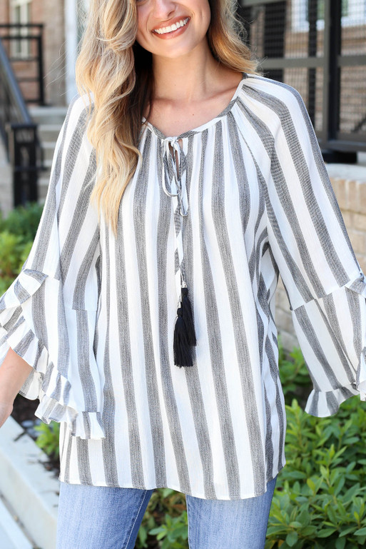 Model wearing Black and White Striped Ruffle Sleeve Tassel Top