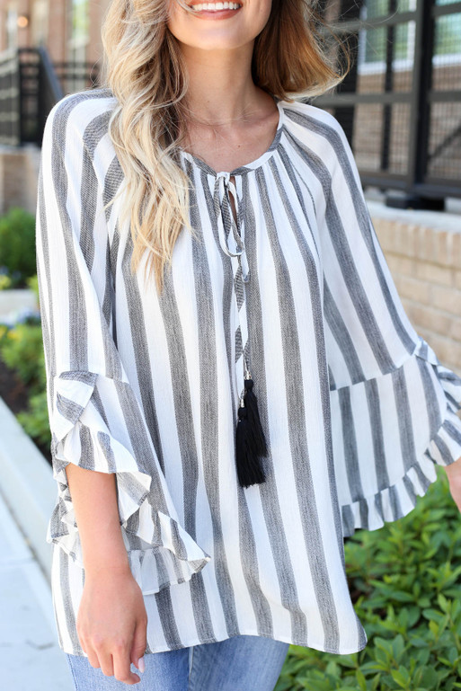 Model wearing Black and White Striped Ruffle Sleeve Tassel Top Detail View