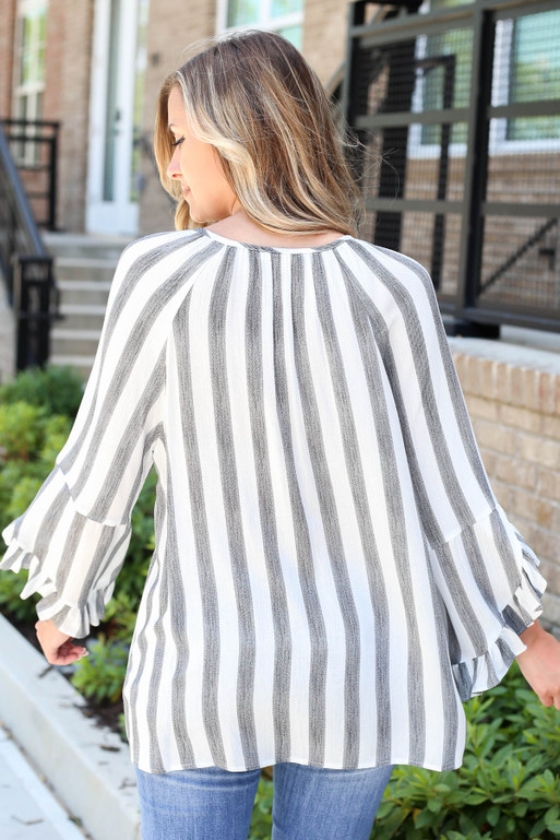 Model wearing Black and White Striped Ruffle Sleeve Tassel Top Back View