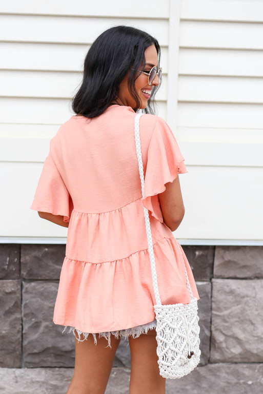 Model wearing Coral Tiered Blouse Back View