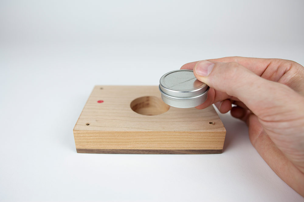 Tiny metal urn capsule is removeable to fill