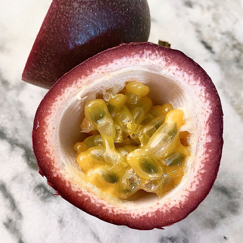 Sliced Organic Passionfruit. Enjoy right out of the rind!