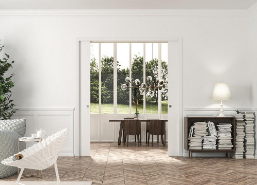 An Eclisse double pocket door system in a room with white wood panelling and architrave but contemporary furniture and lighting