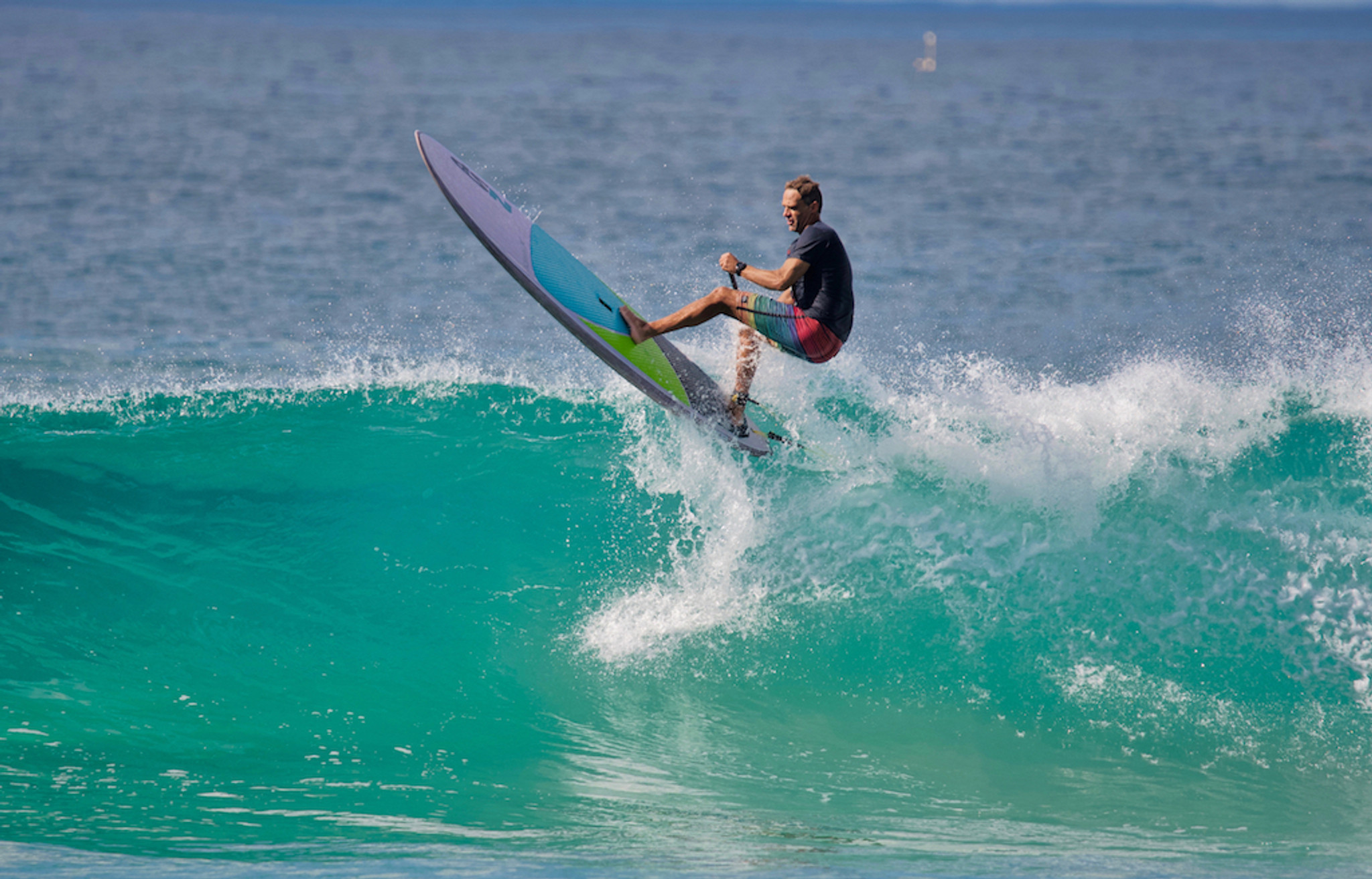 Man shredding waves on a surf SUP board