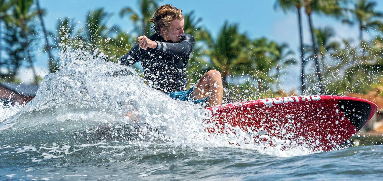 Man carving a wave while SUP surfing