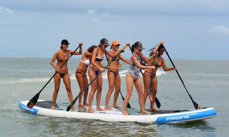 Group of friends paddling on single mega SUP board