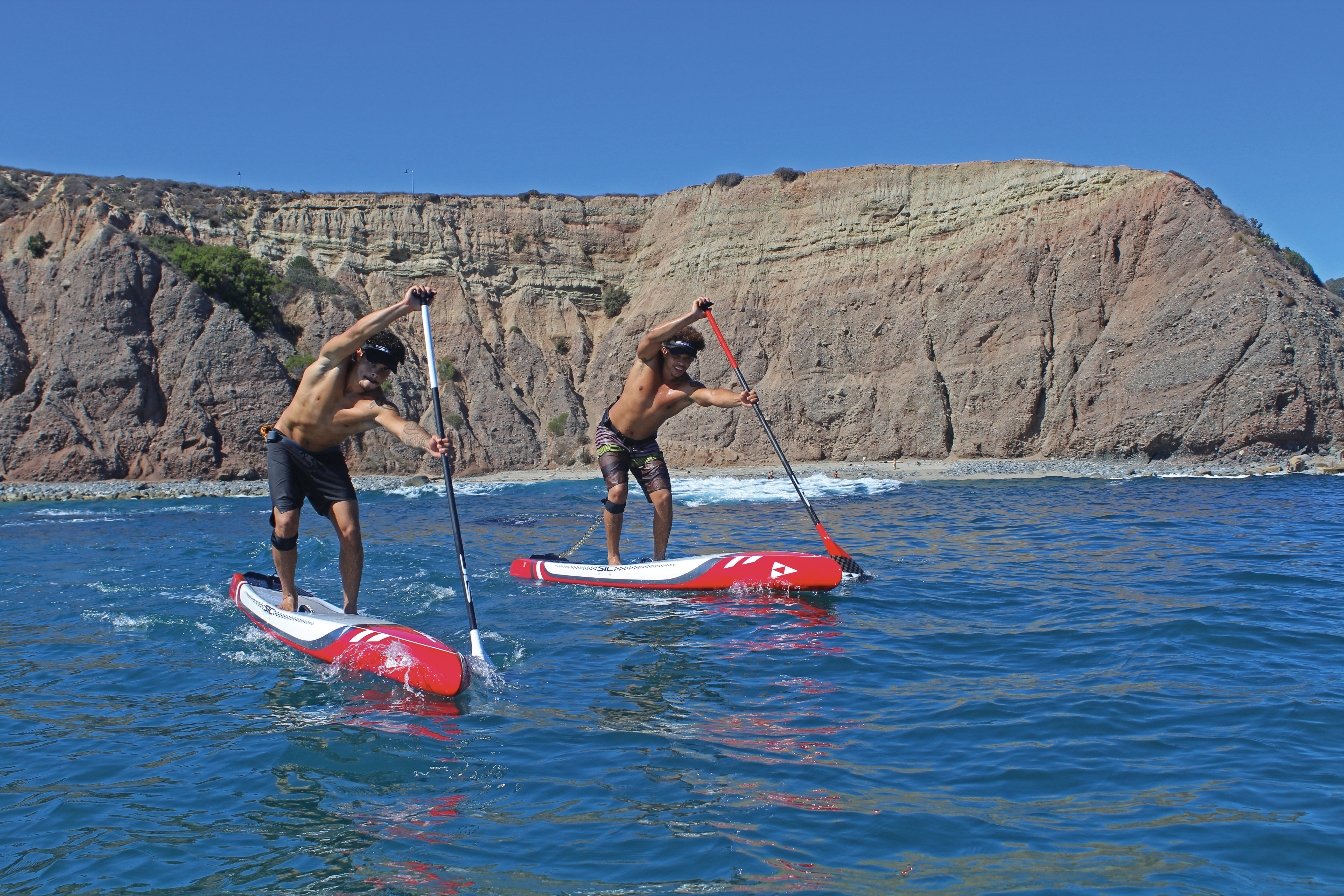 Two men racing on their SIC SUP boards